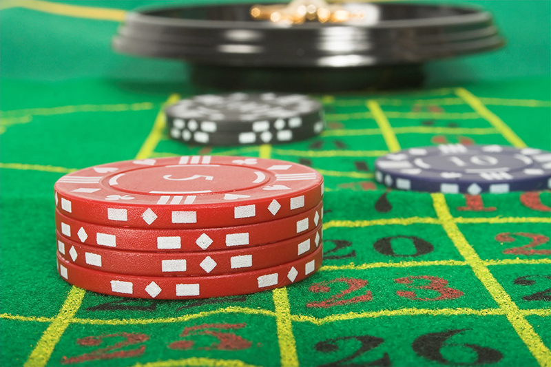 casino tokens and roulette - focus on red tokens